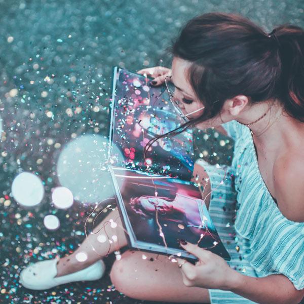 Chica abriendo un libro de moda y efectos luminosos