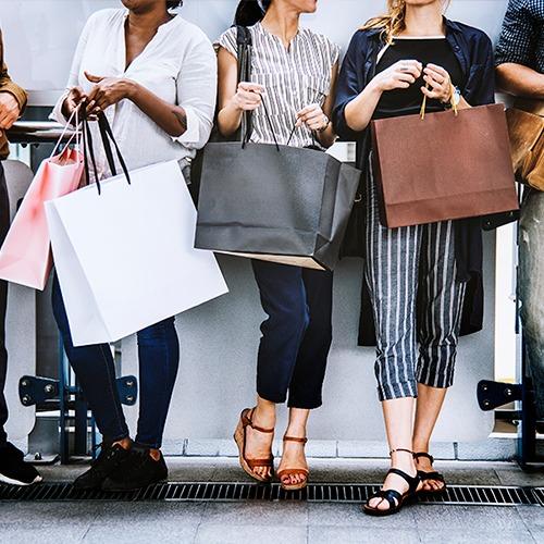 Mujeres de pie con bolsas de compra hablando