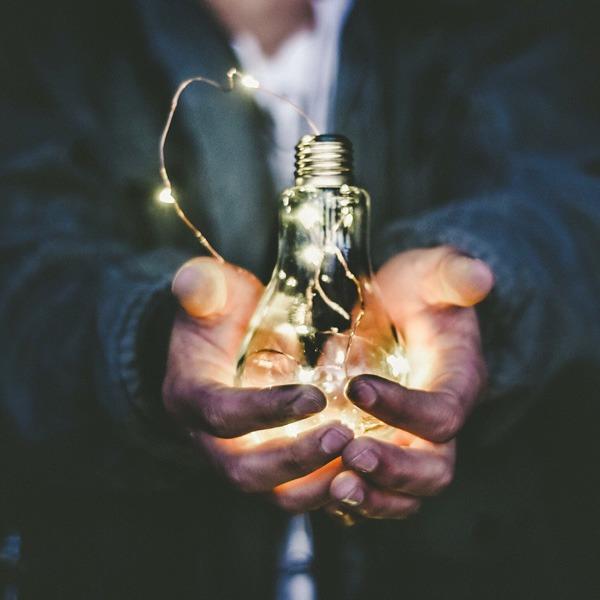 manos sujetando una bombilla y luces
